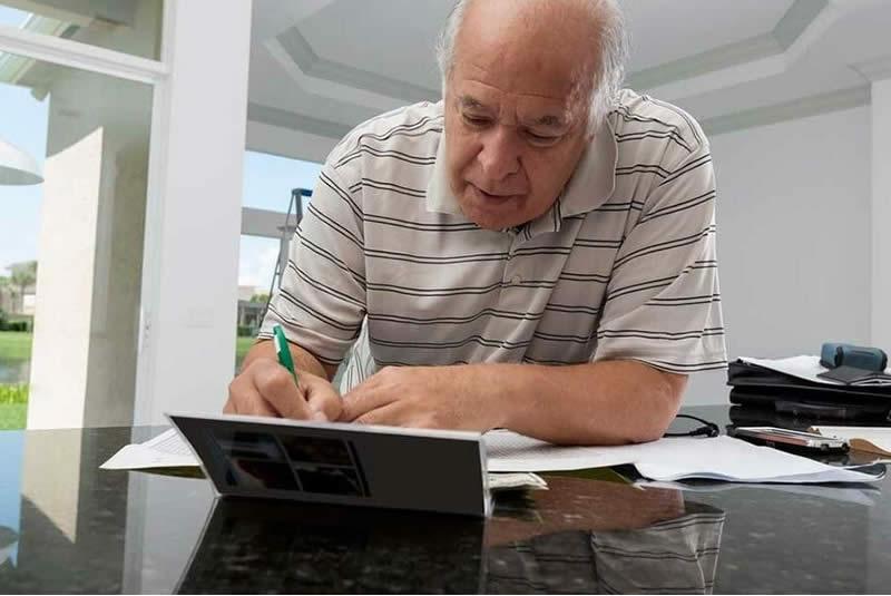 elderly gentleman making notes